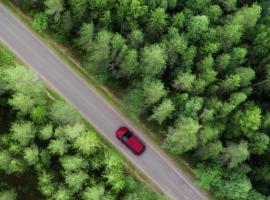 Red electric vehicle driving on a road surrounded by green trees